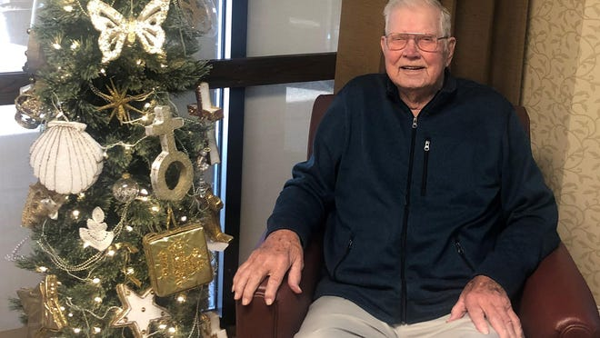 Dale Anderson sits in a chair next to a Christmas tree at the Salina Presbyterian Manor after spending Thanksgiving with his daughters via FaceTime and talking on the phone.