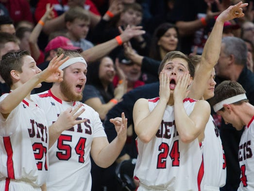 Players on Powers North Central's bench react after