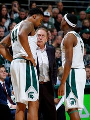 Michigan State coach Tom Izzo, center, talks with Nick Ward, left, and Cassius Winston during the second half of an NCAA college basketball game Savannah State, Sunday, Dec. 31, 2017, in East Lansing, Mich. (AP Photo/Al Goldis)