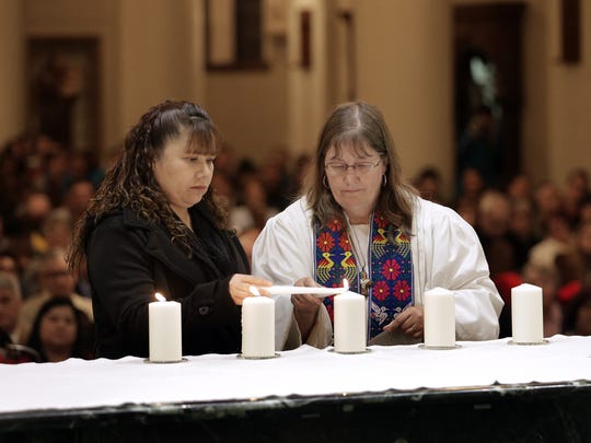 Rev. Deborah Clugy-Soto lights a candle with refugee Maria Alvarado of Mexicanos Auxilary after their testimony Thursday at St. Patrick Cathedral. The Hope Border Institute hosted an interfaith community gathering Thursday to join in solidarity with the immigrants of the El Paso area.