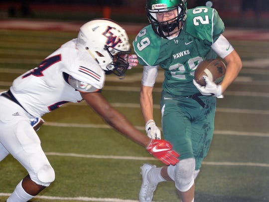 Iowa Park sophomore Kaden Ashlock (29) braces for a hit from SirMichael Veasley (24) of the Waxahachie Life Mustangs Friday night in Gainesville.