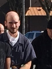 Justin Crandall, left, is taken to jail in February