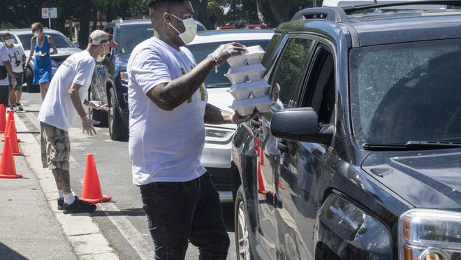 Cars line up for free meals offered at Howley's restaurant in West Palm Beach Saturday, March 28, 2020.