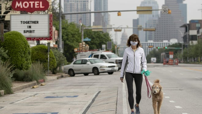 Pat Koem wears a homemade mask -- one she made out of a bandana and two hair elastics -- while walking her dog, Lucy, on South Congress Avenue on April 6.  Austin and Travis County are recommending the use of fabric face coverings when away from home to slow the spread of the coronavirus.
