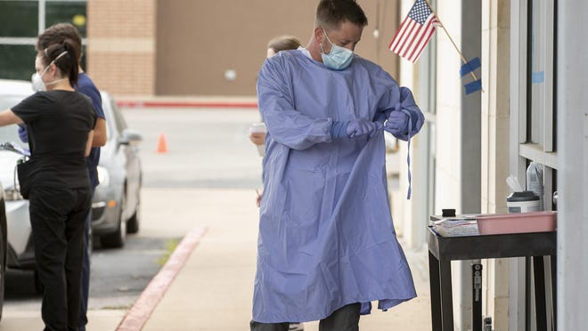 Registered nurse Keith M. prepares to take a sample at a drive-thru COVID-19 test site at Austin Emergency Center on South Lamar Boulevard on July 8.