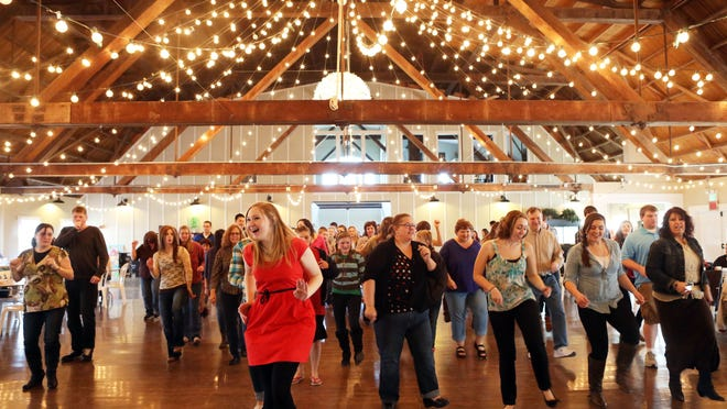 Bartosz (in red), one of the event's organizers, helps lead a dance during a fundraiser for Love Reins Ranch at Green Villa Barn in Independence Feb. 24, 2013.