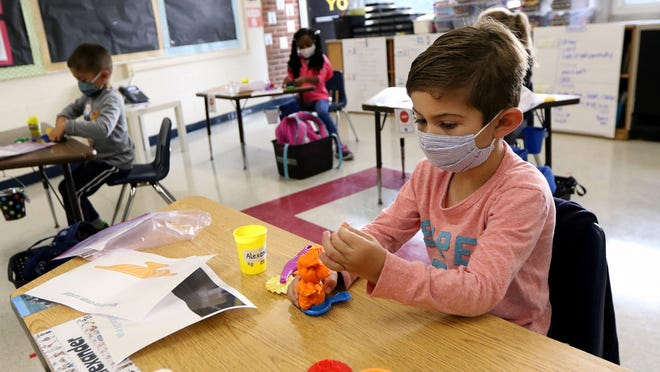 Students, faculty and staff Burlington will start the school year as they ended last year - wearing masks in all indoor spaces. Pictured, Kindergartener Alexander Feola, 5, makes a creation with Play-Doh at Fox Hill School in Burlington, Friday morning, Sept. 18, 2020.