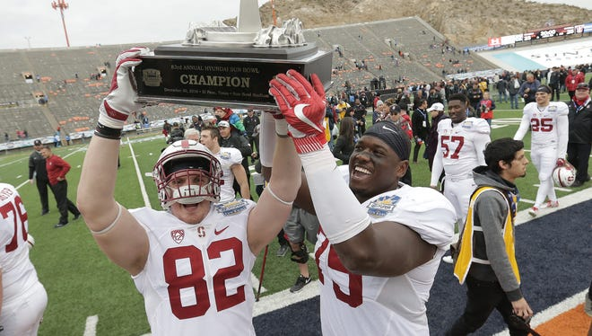 Stanford tight end Kaden Smith, left, and offensive tackle A.T. Hall celebrate with the Sun Bowl trophy after the 83rd Sun Bowl NCAA college football game Friday, Dec., 30, 2016 in El Paso, Texas. Stanford defeated North Carolina 25-23.