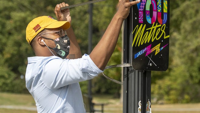 """Che Anderson puts up a new sign on a light post in Elm Park in Worcester on Monday. Anderson installed the inspirational signs that double as works of art as part of the city's """"Give Me A Sign"""" program."""