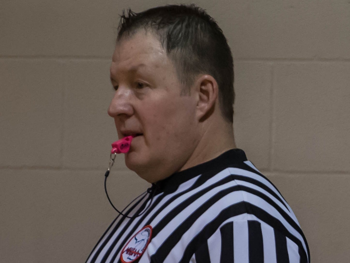 Todd Gooding used a pink whistle during the Marshall-Harper Creek basketball game to honor former Marshall player Kari Searles Jolink who passed away Wednesday after a long fight with cancer.