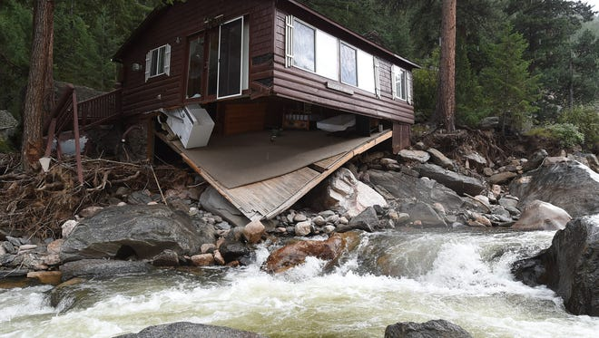 The floor of the Rough'n it Wright cabin in the Big Thompson River, owned by Lynda Wright of Cypress, California, is shown with major damage caused by the September 2013 flood. To the south of the Big Thompson, Lyons marked another step in its flood recover with the opening of a permanent replacement for a damaged bridge over St. Vrain Creek.