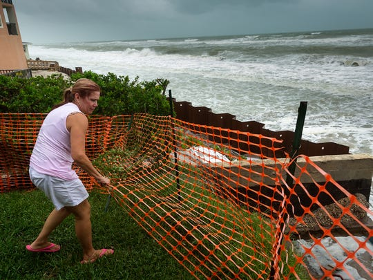 Manasota Key, Fla. homeowner Julie Fugett moves a section of emergency fencing blocking a cliff created by erosion as surf from Hurricane Hermine further undermines the area of critically-eroded beach on Sept. 1, 2016. Several homes and condos on the Charlotte County beach faced structural damage from erosion caused by Tropical Storm Colin in June and their efforts to put an emergency stop to the erosion widely failed during Hurricane Hermine in September.