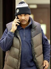Mohammad Choudry, who owns many properties in Milwaukee's central city, talks on his phone at a sheriff's sale.