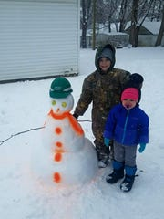 Gage Wozencraft and London Brewer pose for a picture with their snowman!