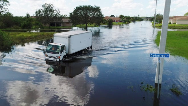 Large vehicles make their way through flooded streets Tuesday, Sept. 12, 2017, near Lehigh High School two days after Hurricane Irma passed through the Lehigh Acres area outside Fort Myers.