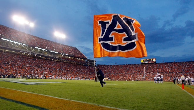 An Auburn cheerleader runs across the field with a flag after a touchdown during the first half of an NCAA college football game against San Jose State.