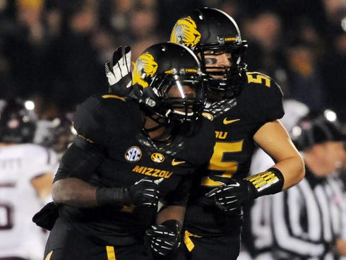 Missouri Tigers defensive back John Gibson is congratulated by wide receiver Marcus Lucas after Gibson recovered a fumble during the first half at Faurot Field.