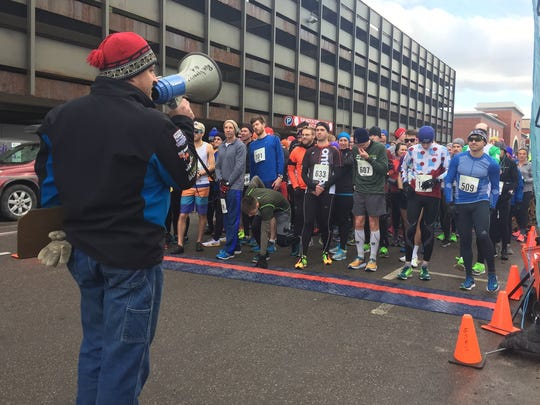 A representative of RunVermont speaks to the crowd of runners before the First Run 5K on Sunday Jan. 1, 2017 in Burlington.