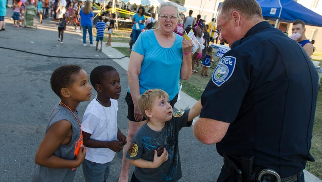 Lieutenant Joe Platzer hands out police badge pins Tuesday, Aug 2, 2016 during National Night Out in Port Huron.