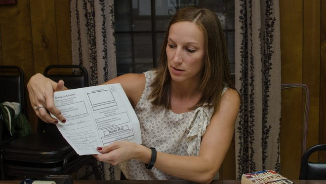 Pensacola attorney Lauren Lewis, who volunteers with the Open Books Prison Book Project, shows a form detailing an inmate's book requests on Wednesday, May 3, 2017, at the Open Books bookstore.