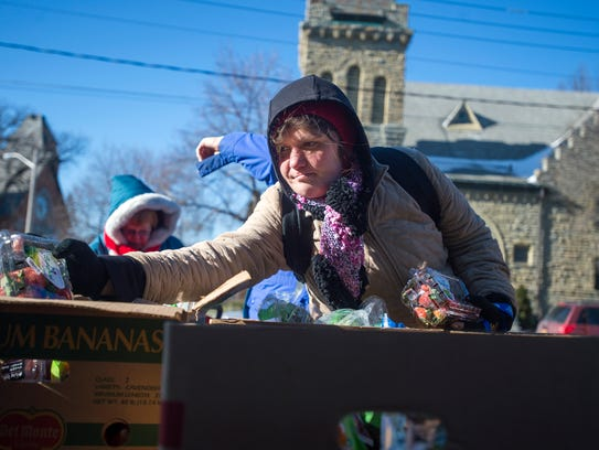 Binghamton resident Melissa Bower, 35, reaches for a package of strawberries at a mobile food pantry held by the Food Bank of the Southern Tier in downtown Binghamton.