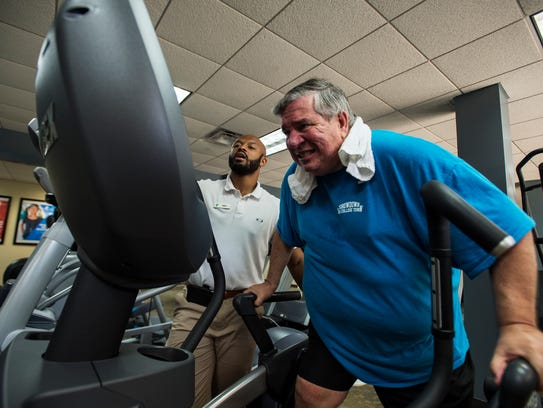 Ken Mullinax works out on an elliptical under the instruction