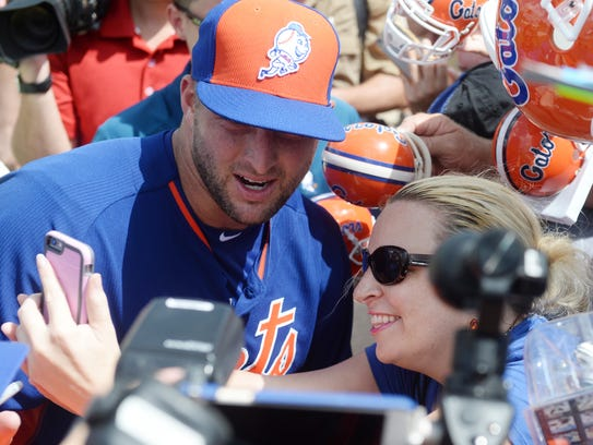 Tim Tebow poses with a fan on the day of his first