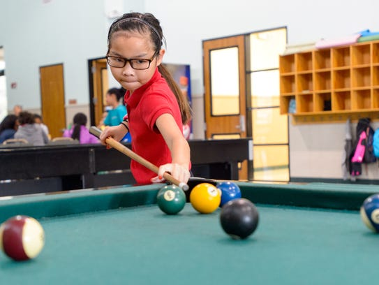 Sarah Domingue playing pool at the Boys and Girls Club.