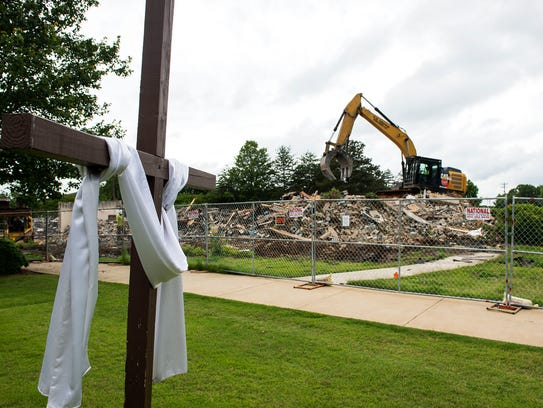 An excavator digs through rubble at Advent United Methodist