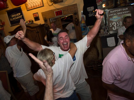 Scott Watson, of Indiantown, (center) receives a hug from Ande Bauzenberger, of Indiantown, (left) as he celebrates with members of the Indiantown Independence Group after Indiantown's incorporation vote passed, at JR's BBQ and Saloon on Tuesday, Nov. 7, 2017, in Indiantown.