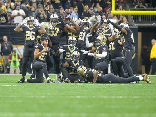 Saints defense celebrates by posing for a photo after