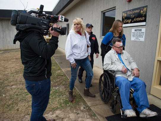 A man is wheeled into Pine Ridge Middle School, which