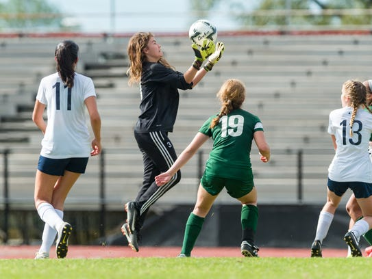 ESA keeper Ella Frantzen goes high to box to snag a shot for a save during the Lady Falcons' 2-0 loss to Newman in the Division IV state soccer finals Friday.