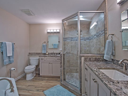 The master bath has a glass enclosed shower, a soaking