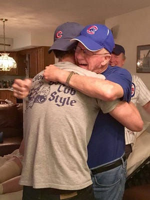 "Erwin ""Erv"" Schreiber hugs his grandson Paul Schreiber after the Cubs won the World Series."