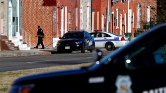An officer walks behind a police line near the scene of the shooting death of Baltimore Police Detective Sean Suiter on Nov. 17.