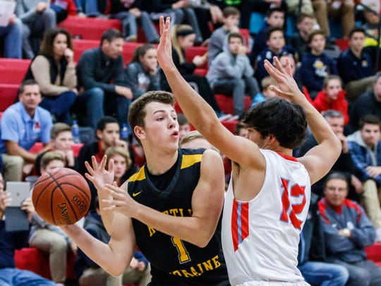 Kettle Moraine sophomore Nolan Dahmen (1) looks to pass around Arrowhead's JJ Oehmcke (12) during the game at Arrowhead in December 2017.