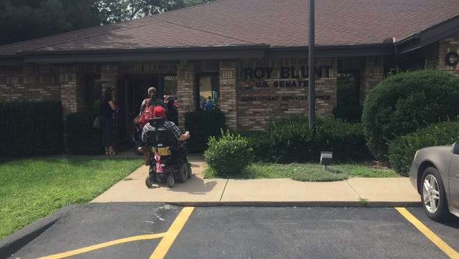 A group comprising some people with disabilities in wheelchairs and local health care activists enter Sen. Roy Blunt's office on East Sunshine Street on Tuesday, Aug. 16, 2017.