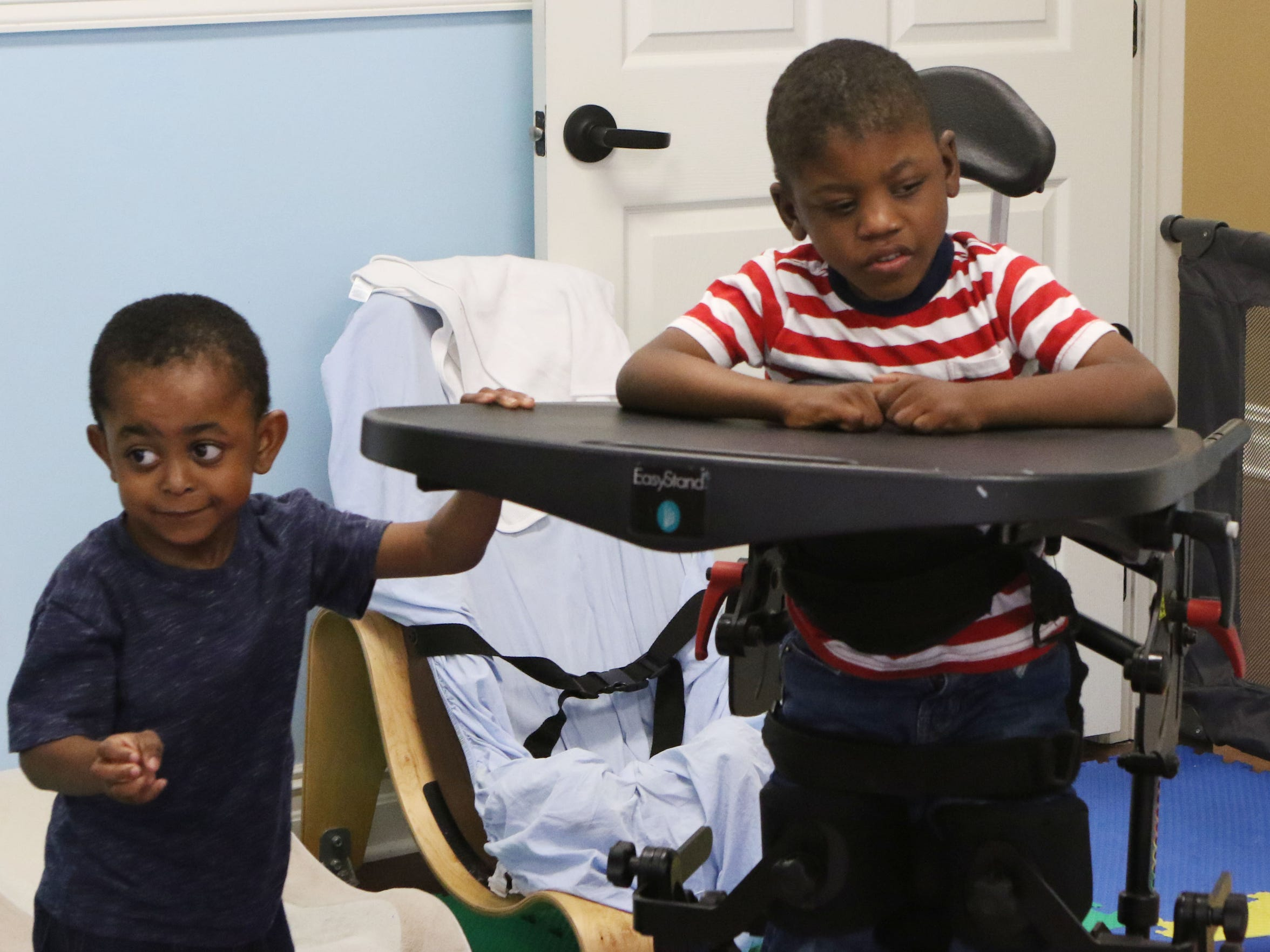 Antron Patterson, 3, left, tries to get the attention