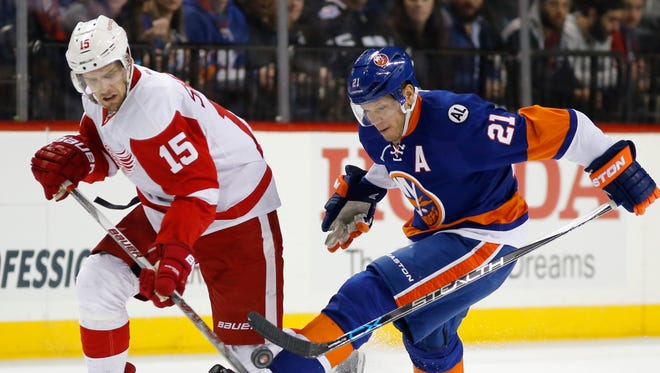 New York Islanders right wing Kyle Okposo, right, kicks the puck with his skate as Detroit Red Wings center Riley Sheahan closes in in New York on Jan. 25, 2016.