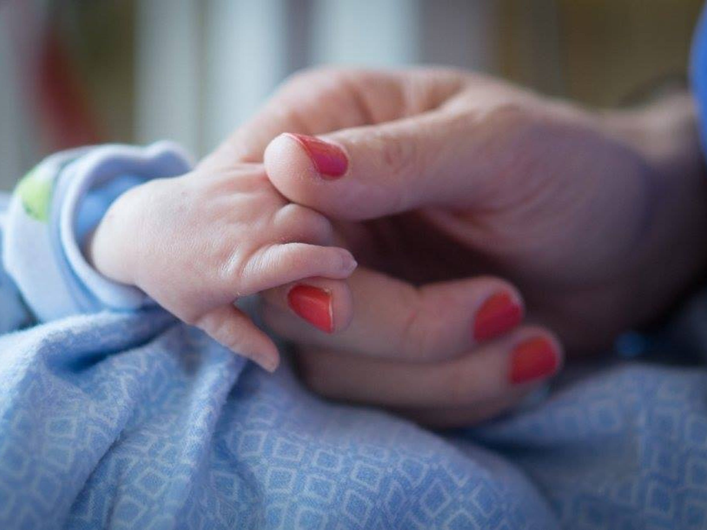 Katie Butler holds her son Dewey's hand.