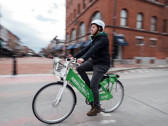 Cyclist using Greenride Bikeshare bicycle