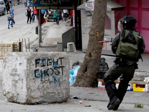 An Israeli border policeman aims his weapon toward Palestinian stone throwers,during clashes in the West Bank city of Hebron earlier this year.