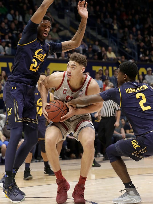 Stanford forward Reid Travis, center, drives between California forward Marcus Lee (24) and guard Juhwan Harris-Dyson (2) during the first half of an NCAA college basketball game in Berkeley, Sunday, Feb. 18, 2018. (AP Photo/Jeff Chiu)