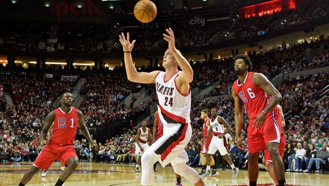 Portland Trail Blazers center Mason Plumlee, center, reaches for the ball in front of Los Angeles Clippers center DeAndre Jordan, right, and forward Lance Stephenson, left, during the first half of an NBA basketball game in Portland, Ore., Friday, Nov. 20, 2015.