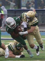 DePaul quarterback Taquan Roberson is tackled by Evan