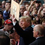 Donald Trump prepares to autograph a cardboard with two dollars taped to it as he greets supporters during a campaign event at Hampshire Hills Athletic Club in Milford, Iowa, on Feb. 2, 2016.