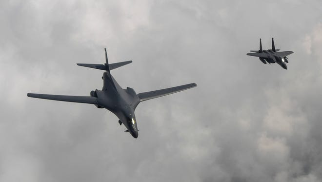 A U.S. B1-B bomber is escorted by a South Korean F-15K fighter as they fly over South Korea during a 10-hour mission from Andersen Air Force Base, Guam, into Japanese airspace and over the Korean Peninsula on July  30, 2017.