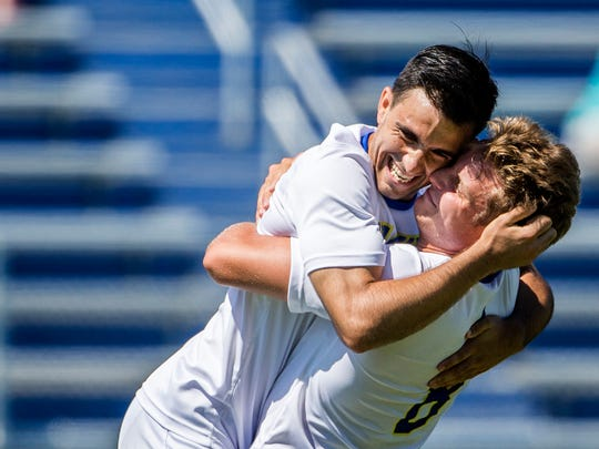 Delaware's Jaime Martinez (No. 8) hugs teammate Guillermo Delgado after Delgado put a shot past Fordham keeper Rashid Nuhu for a goal in the first half of Delaware's 1-0 win over Fordham at Grant Stadium at the University of Delaware on Sunday afternoon.