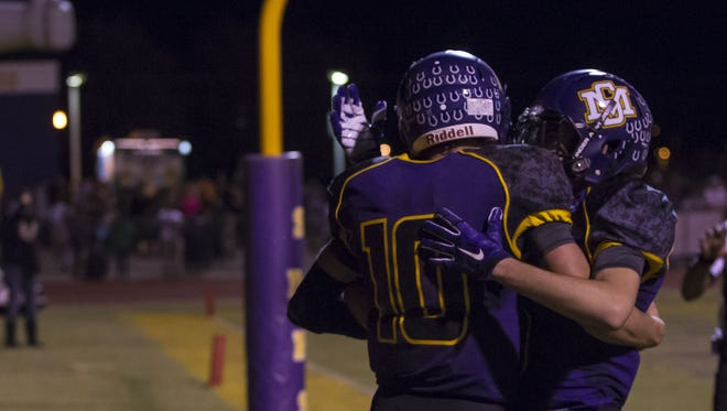 Sunrise Mountain junior quarterback Chase Cord celebrates with a teammate after he runs the football in for a touchdown in a football game against Glendale Cactus at Sunrise Mountain High School in Peoria on Friday, Nov. 6, 2015. Sunrise Mountain leads Cactus 36-6 at the half.